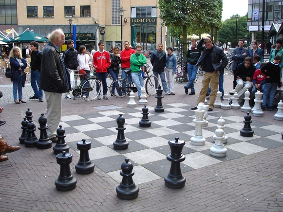 Two men play chess with a huge outdoor set